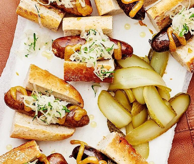 Kryddkorvar och surkål i baguette med saltgurka och senap