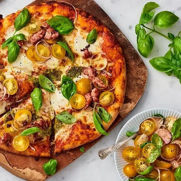 Pizza med pesto, mozzarella, salsiccia och tomatsallad