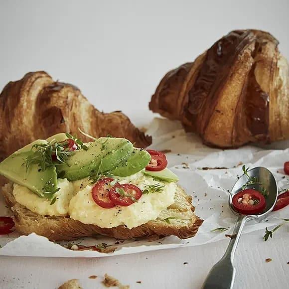 Croissant till frukost med krämig äggröra, avokado och chili