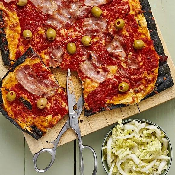 Svart pizza med hummus och tomatsås