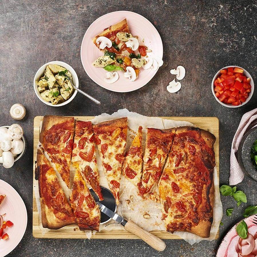 Pizza med mozzarella och olika toppings