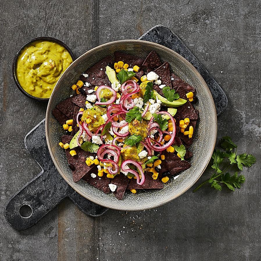 Blue corn tortillachips med bönor, avokado och picklad lök
